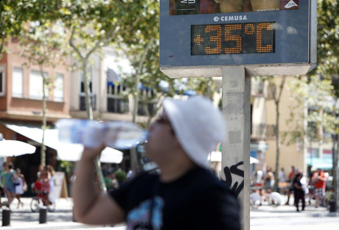 Un hombre bebe agua ante un termómetro que marca los 35 grados, en Barcelona.