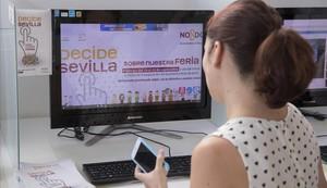 Una empleada del Ayuntamiento de Sevilla ante la web abierta para votar sobre la duración de la Feria de Abril.