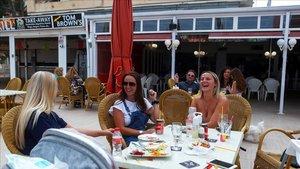Jóvenes almuerzan en una terraza playera.