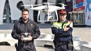 Dos de los agentes de la policía autonómica, el operador del dron (izquierda) y el radiofonista, realizan una demostración de vuelo delante del recinto ferial donde se celebrará el Mobile, este jueves.