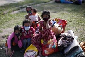Niñas sostienen sus pertenencias en un espacio abierto tras el terremoto de 7,3 grados en la escala Richter de este martes.