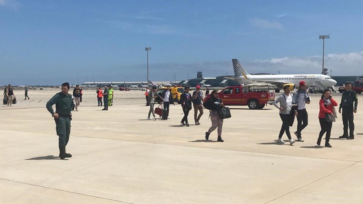 Los pasajeros del avión de la compañía Vueling que ha aterrizado de emergencia en el aeropuerto de Barcelona por una falsa amenaza de bomba.