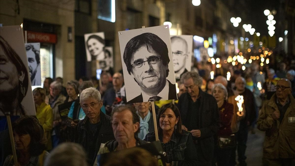 Manifestantes independentistas exhiben carteles con los rostros de Puigdemont y el resto de líderes del 'procés', el pasado octubre, en Barcelona.