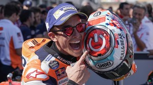 Marc Márquez señala, feliz, el interruptor que tiene dibujado sobre su casco.