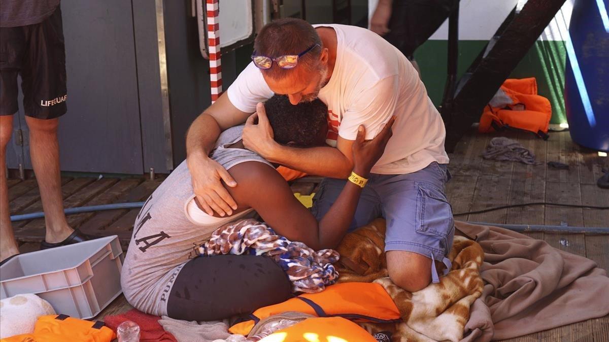 Un miembro de Open Arms consuela a una migrante en el buque.