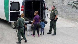 Oficiales migratorios de los EEUU detienen a una mujer y su hijo.