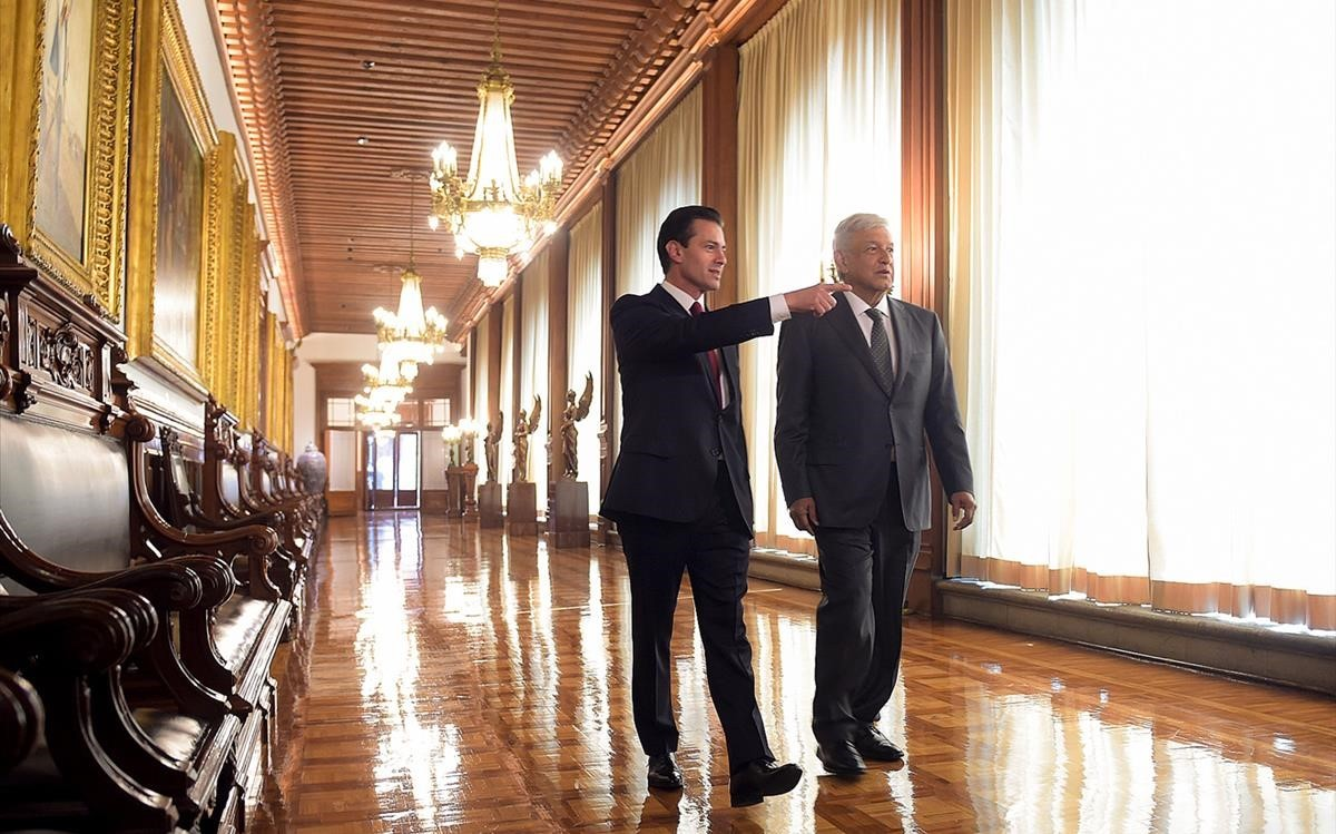 Peña Nieto acompaña a López Obrador por el palacio presidencial.