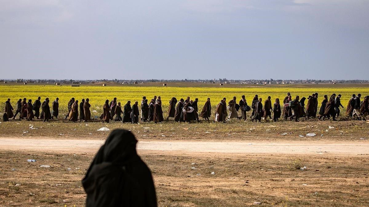 sospechosos de ser combatientes grupales de IS del Estado Islámico caminan juntos hacia un punto de detección para los recién llegados dirigidos por las Fuerzas Democráticas Sirias respaldadas por Estados Unidos donde se sospecha que los yihadistas