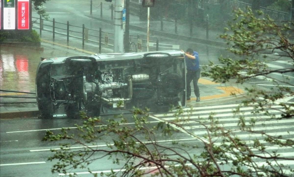 Un hombre junto a un coche volcado por los fuertes vientos en una calle de Osaka.