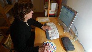 Una mujer consulta internet en su ordenador.