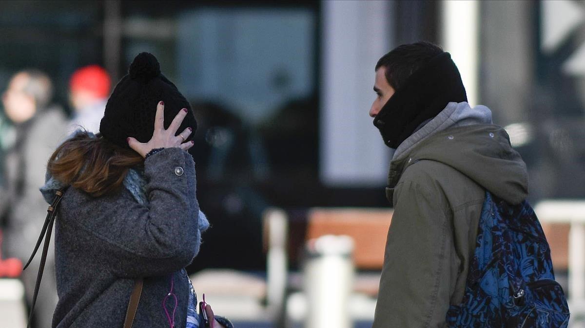 Una mujer y un hombre, protegidos del frío por gorro y bufanda, se cruzan en la Rambla del Poblenou de Barcelona, el 11 de enero del año pasado, cuando se produjo otro descenso brusco de las temperaturas.