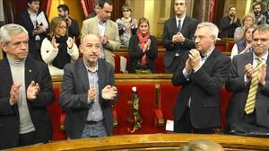 Los diputados del Parlament aplauden en homenaje a Muriel Casals,con una rosa blanca en su escaño.