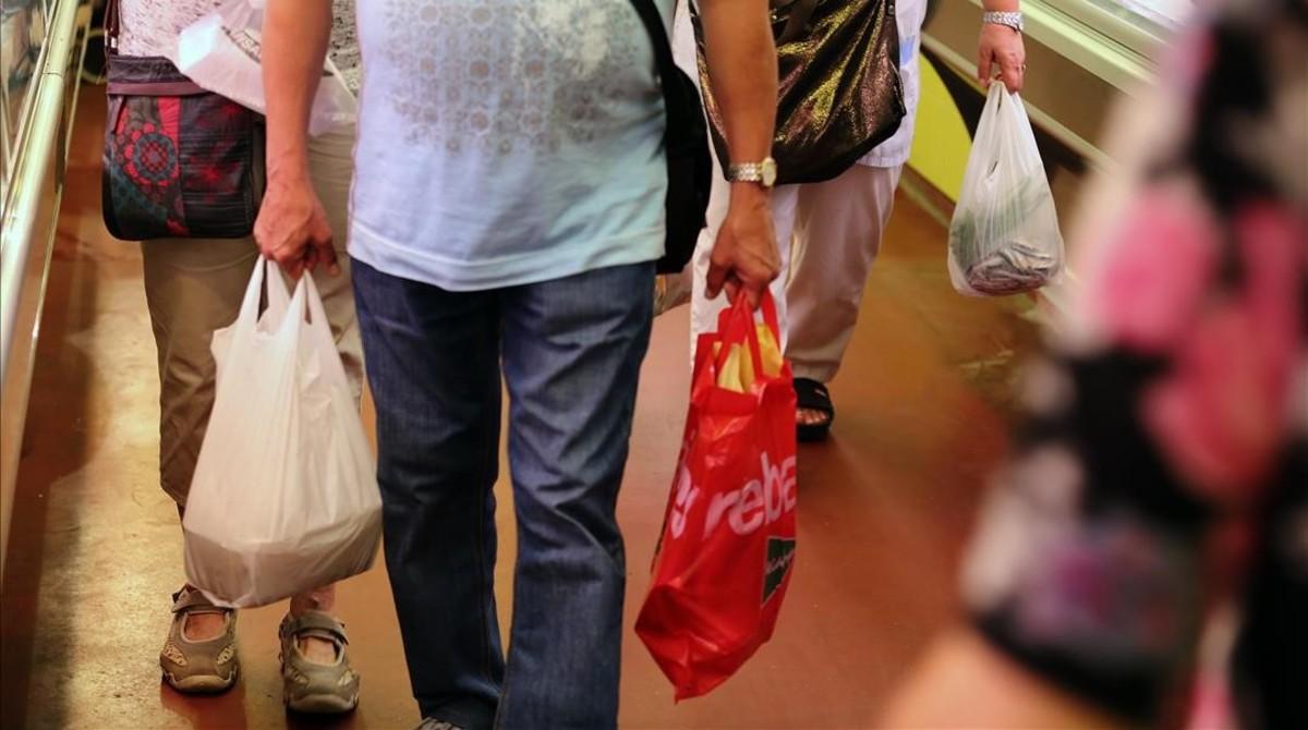 Un consumidor con bolsas de plástico.