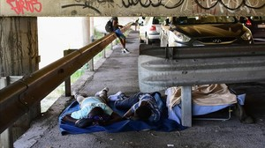 Unos inmigrantes tratan de descansar en el párking ubicado bajo un puente en la localidad italiana de Ventimiglia.