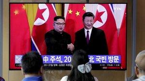 Unos transeúntes observan un programa de TV en el que aparecen el presidente chino Xi Jinping saludando al líder norcoreano Kim Jong-un en Pionyang.