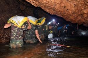 Varios miembros de un equipo de rescateintentan drenar el agua de la cueva Tham Luang en Khun Nam Nang Non Forest Park (Tailandia).