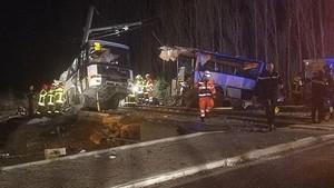 Varios trabajadores retiran los restos del autobús que se ha partido en dos tras el choque con el tren.