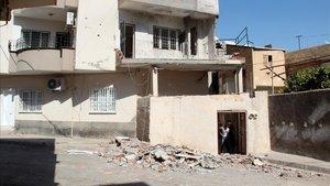 Un vecino limpia escombros en su casa de Nusaybin tras un ataque con morteros desde Siria, el pasado lunes.