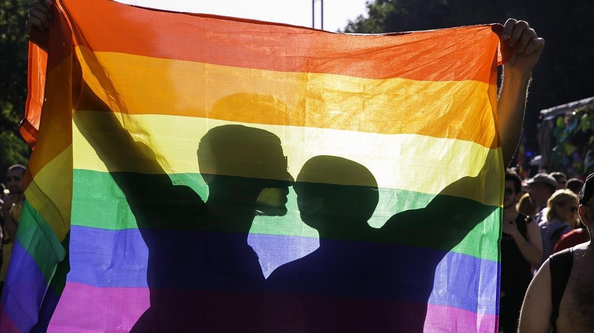 Una pareja se besa tras una bandera arcoíris durante la manifestación del orgullo LGBTI+ del pasado junio en Barcelona