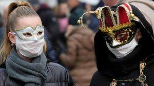 Asistentes con mascarillas protectoras en el carnaval de Venecia, queha quedado suspendido.