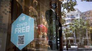 Sello de Covid Free en el escaparate de un establecimiento adscrito a la iniciativa, en el paseo de Gràcia.