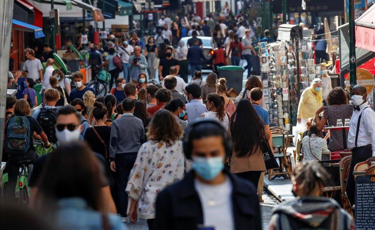 Paseantes con mascarilla en una calle del centro de París.