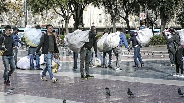 Un grup de manters a la plaça de Catalunya.