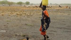 Una mujer desplazada interna en Sudán del Sur lleva agua al campamento en el que se refugia.