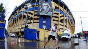 Un aficionado pasa por delante del estadio bajo la lluvia torrencial.