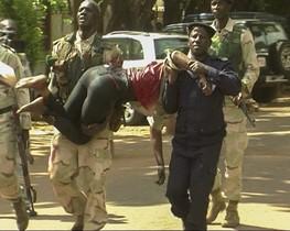 Personal d'emergènciesde Mali traslladauna dona ferida al sortirde l'hotel Radisson.