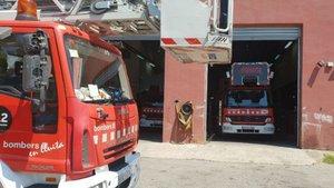 Una camión con autoescalera, en un parque de bomberos.