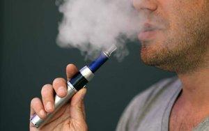 Una persona fumando con un cigarrillo electrónico.