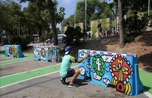 Kamil Escruela, en el aparcamiento del parque Güell, da unos repasos a una de sus obras.