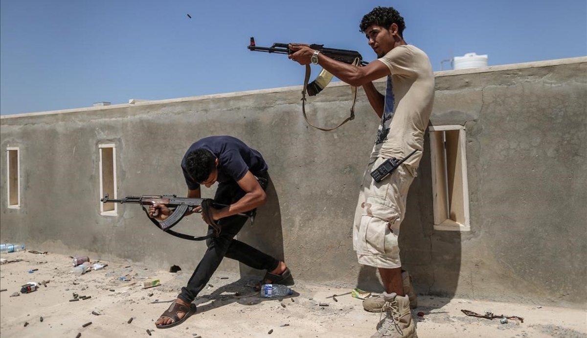 Combatientes de las tropas del Gobierno reconocido internacionalmente disparan sus armas durante un enfrentamiento con las fuerzas del autodenominado Ejército Nacional Libio, lideradas por el general Haftar.