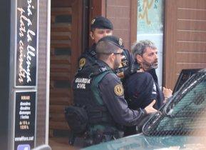 Dos agentes de la Guardia Civil se llevan un detenido en Sabadell en el marco de la operación que ha acabado con nueve miembros de CDR arrestados.
