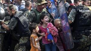 Dos niños lloran en un enfrentamiento entre inmigrantes y policía en la frontera de Grecia y Macedonia, en el 2015.