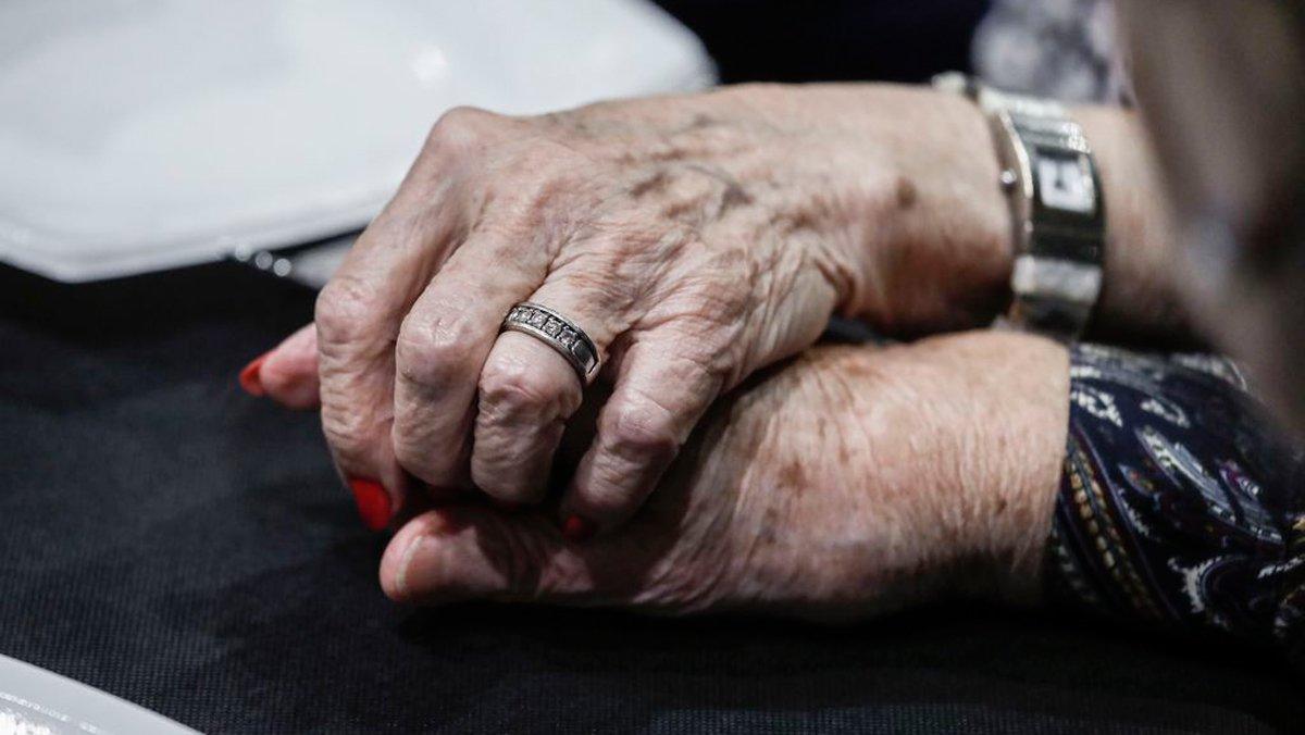 Dos personas mayores se cogen de la mano.