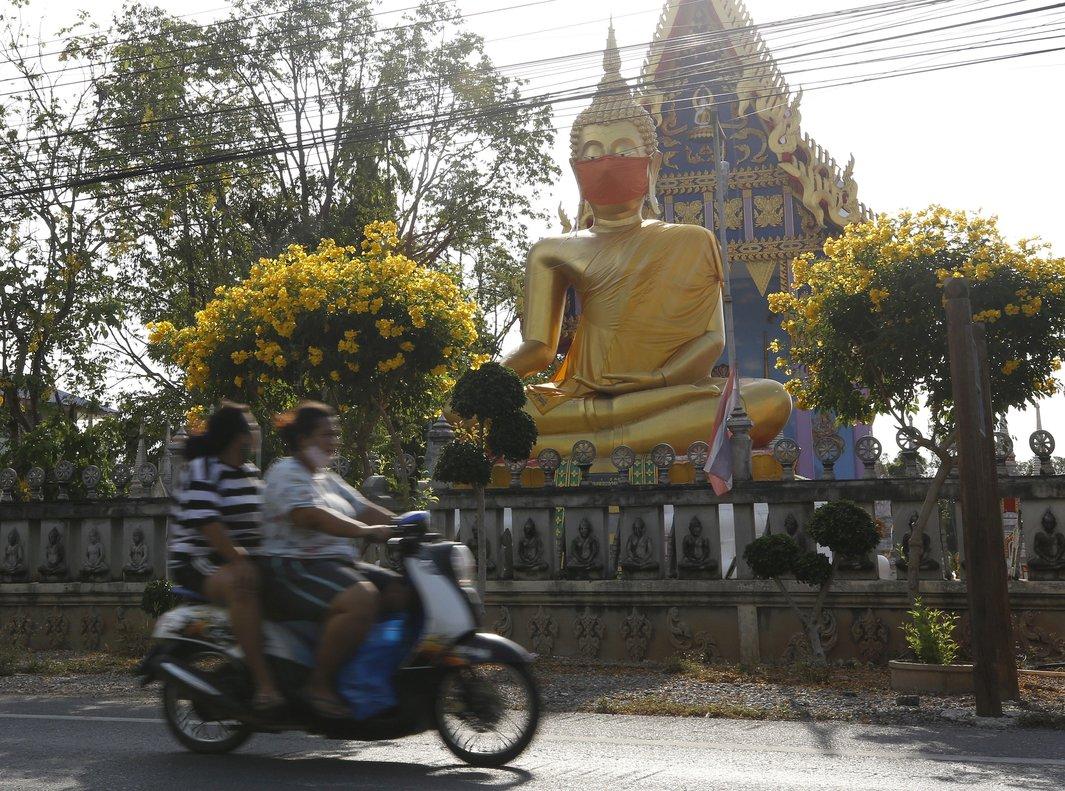 Dos tailandesescirculan en moto delante de una estatua de Buda con mascarilla en las afueras de Bangkok.