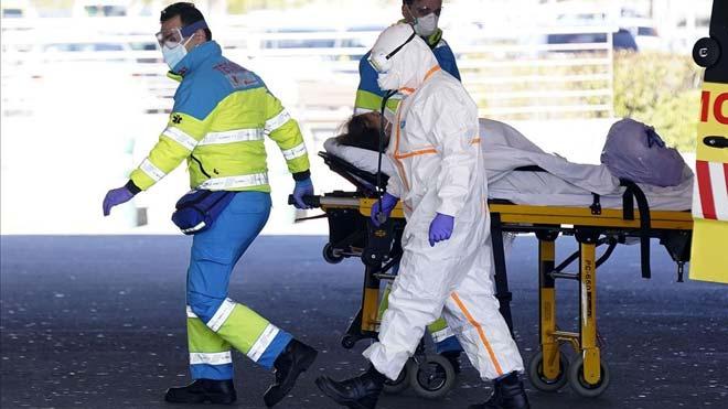España vuelve a superar los 900 muertos por coronavirus en un día y ya se rozan los 11.000. En la foto, enfermeros trasladan a una mujer mayor concoronavirus a Urgencias del Hospital Puerta de Hierro en Majadahonda, Madrid.