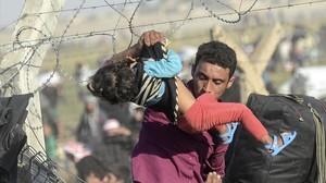 Un refugiado sirio hace pasar a un bebé por la frontera.