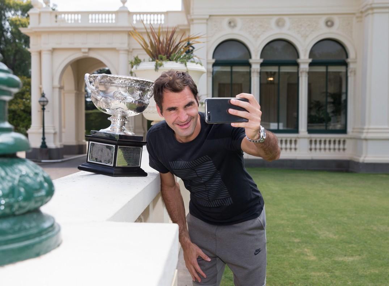 Roger Federer se hace un selfie con el trofeo conquistado en Australia.
