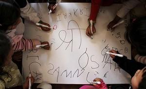 Un grupo de niños escriben letras en una cartulina durante la conmemoración del festival 'Bsant Panchmi', en un jardín infantil en Katmandú (Nepal). Los estudiantes nepalíes visitan los templos durante este día para rendir culto a la Diosa Saraswati, esposa de Brahma, diosa del aprendizaje y la sabiduría.