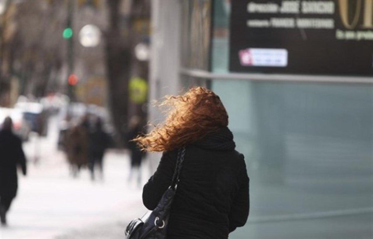 Una mujer afectada por el frío ylos fuertes vientos.