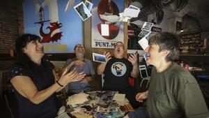 Nuria, Luis Miguel, Jordi y Carina, cuatro postcrossers de Barcelona, rodeados de algunas de las postales que han recibido.