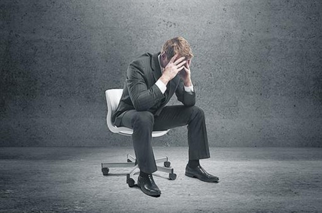 Hombre sentado en una silla preocupado.