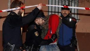 La Policía Nacional acompaña a uno de los detenidos por el tiroteo de Carabanchel.