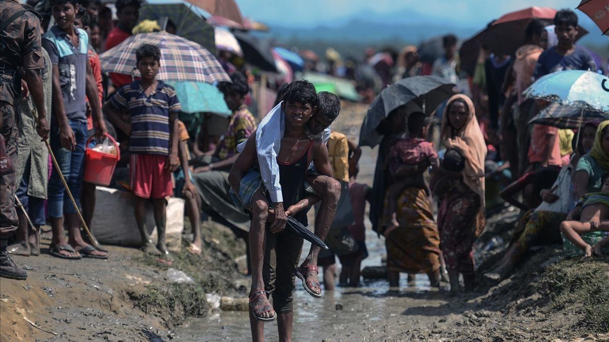 Un joven refugiado rohingya lleva a cuestas un hombre mayor en una zona cercana al lado bangladesí de la frontera con Birmania, tras cruzar el río Naf, el 17 de octubre.