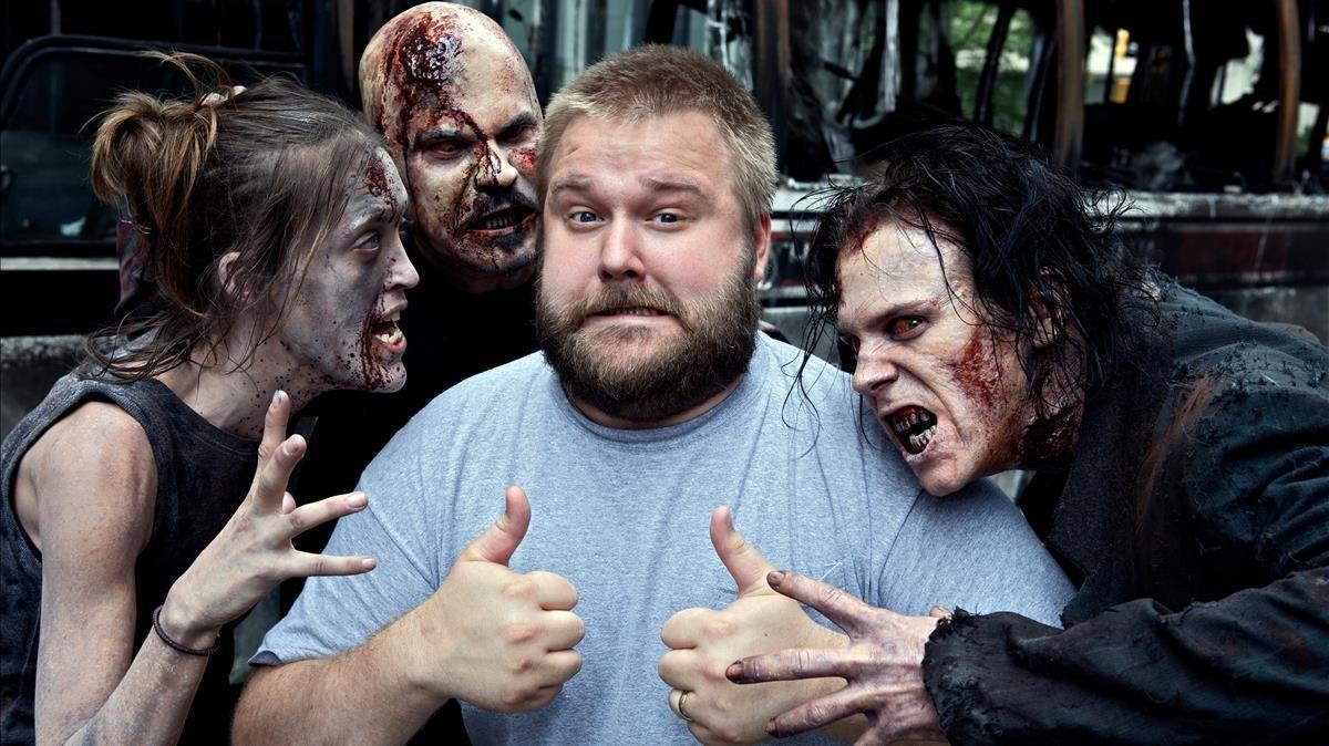 Robert Kirkman, rodeado de algunas de las criaturas protagonistas de The walking dead.