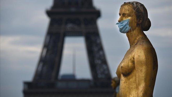 Máscaras en las estatuas de la explanada deTrocadero, durante el cierre contra el brote de coronavirus. La torre Eiffel es visibleal fondo.