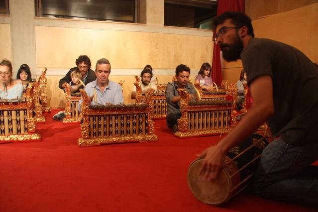 Un músico enseña como se toca el Gamelan a los visitantes del Museu de la Música.